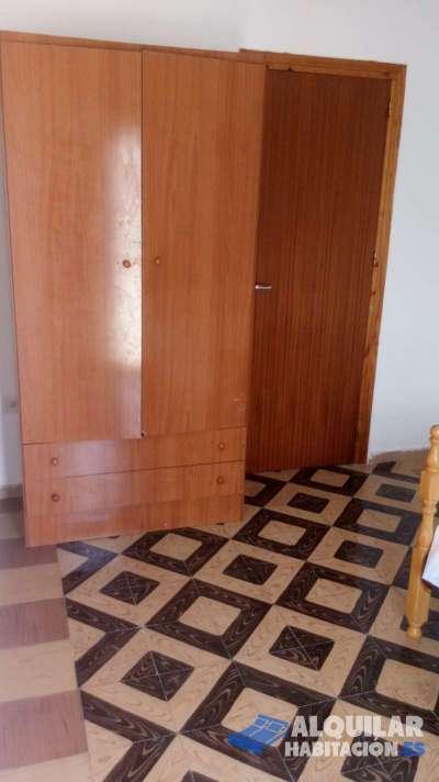 habitacion con una pequeña terraza que da a la calle , cama , armario , mesita y escritorio , ampli